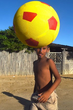 A boy from the Wayuu indigenous etnia plays soccer at a Christmas event where members of Kiwanis Foundation gave away gifts to Wayuu kids at the Manhaim Rancheria in Cabo de la Vela, Guajira department, Colombia, on December 23, 2017. Photo by Joaquin Sarmiento