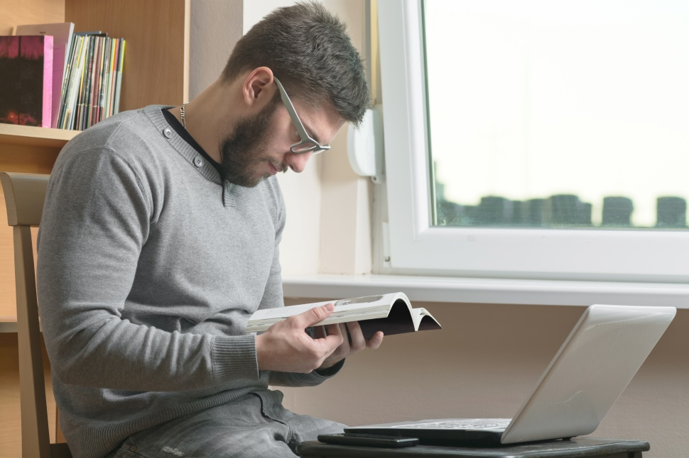 Young adult man reading book at office